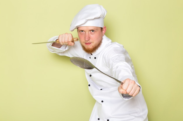 A front view young male cook in white cook suit white head cap holding knife and big silver spoon