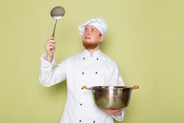 Un cuoco maschio giovane di vista frontale in vestito bianco bianco del cappuccio del vestito del cuoco bianco che tiene la casseruola d'argento e metallica con il grande cucchiaio d'argento