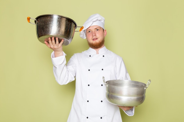 A front view young male cook in white cook suit white head cap holding silver and metallic saucepans