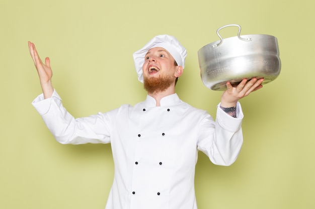 A front view young male cook in white cook suit white head cap holding silver saucepan amused excited