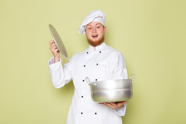 A front view young male cook in white cook suit white head cap holding silver saucepan excited