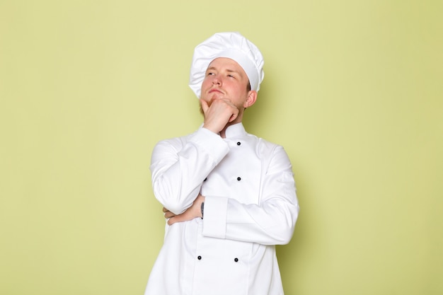 A front view young male cook in white cook suit white head cap posing thinking