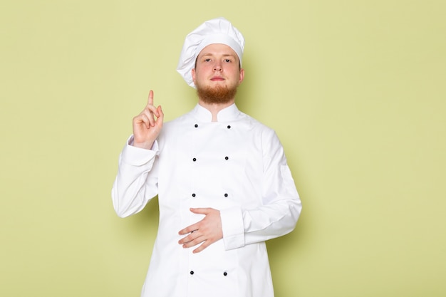 A front view young male cook in white cook suit white head cap raising his finger
