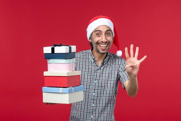 正面図赤い背景の上のプレゼントの数を数える若い男性