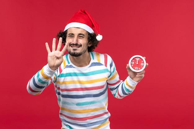 赤い壁の赤い時間の年末年始の数を示す正面図若い男性のカウント