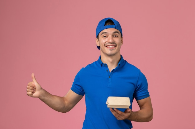 Front view young male courier in blue uniform cape holding delivery food package on pink wall