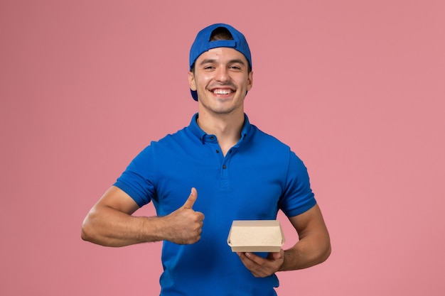 Giovane corriere maschio di vista frontale in mantello blu uniforme che tiene il pacchetto di cibo di consegna sulla parete rosa