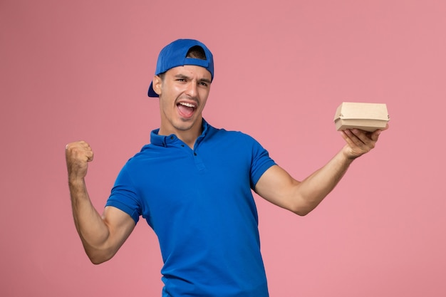 Front view young male courier in blue uniform cape holding delivery food package rejoicing on pink wall