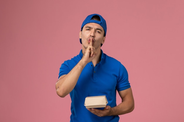 Front view young male courier in blue uniform cape holding delivery food package showing silence sign on pink wall