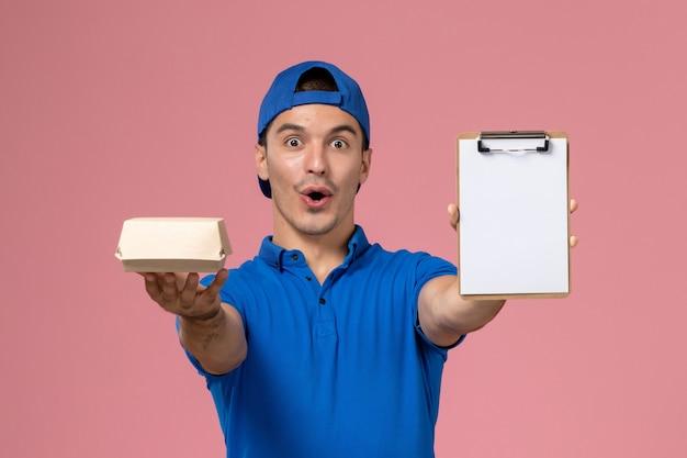 Giovane corriere maschio di vista frontale in capo uniforme blu che tiene piccolo pacchetto di cibo di consegna e blocco note sull'impiegato di servizio scrivania rosa chiaro che consegna azienda
