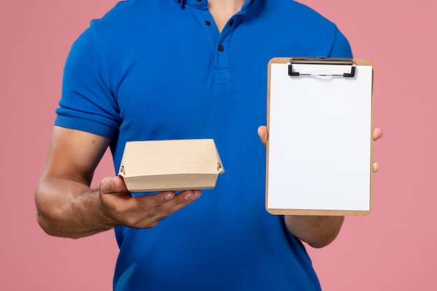 Front view young male courier in blue uniform cape holding little delivery food package and notepad on light-pink wall