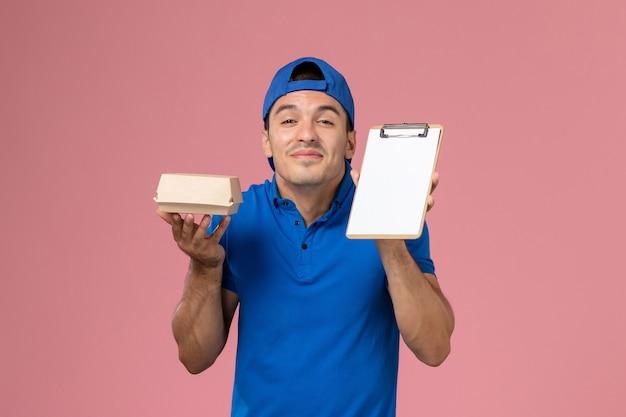 Giovane corriere maschio di vista frontale in capo uniforme blu che tiene poco pacchetto dell'alimento di consegna e blocchetto per appunti sulla parete rosa-chiaro
