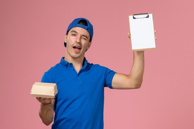 Front view young male courier in blue uniform cape holding little delivery food package and notepad on the light-pink wall