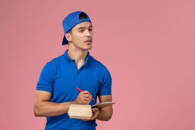 Front view young male courier in blue uniform cape holding little delivery food package and notepad writing notes on the light-pink wall