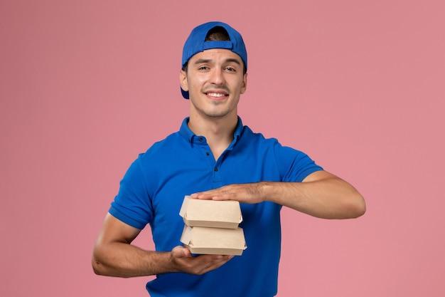 Giovane corriere maschio di vista frontale in capo uniforme blu che tiene piccoli pacchetti dell'alimento di consegna sulla parete rosa