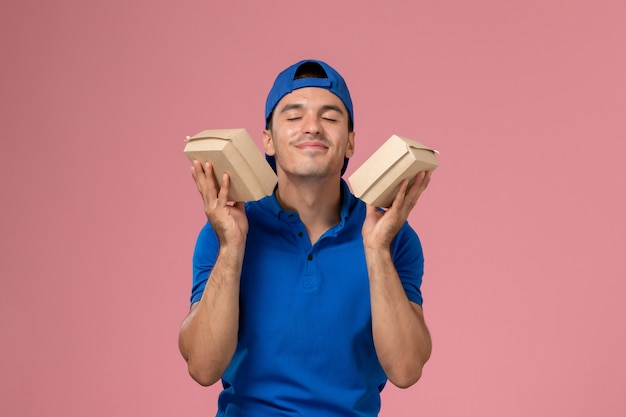 Front view young male courier in blue uniform cape holding little delivery food packages on the pink wall
