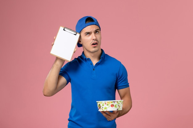 Front view young male courier in blue uniform cape holding notepad and round delivery bowl just thinking on pink wall