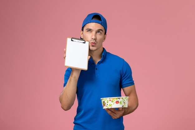 Front view young male courier in blue uniform cape holding notepad and round delivery bowl thinking on pink wall