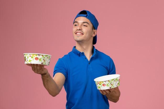 Giovane corriere maschio di vista frontale in capo uniforme blu che tiene le ciotole rotonde di consegna sulla parete rosa-chiaro