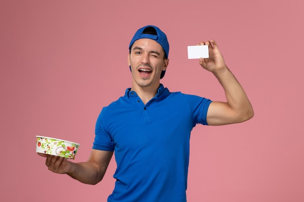 Front view young male courier in blue uniform cape holding white card and round delivery bowl on light pink wall