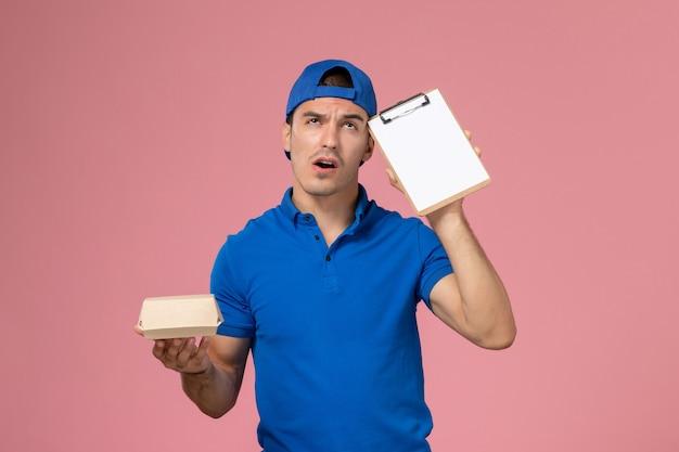 Giovane corriere maschio di vista frontale in capo uniforme blu che pensa e che tiene poco pacchetto di cibo di consegna e blocco note sulla parete rosa chiaro
