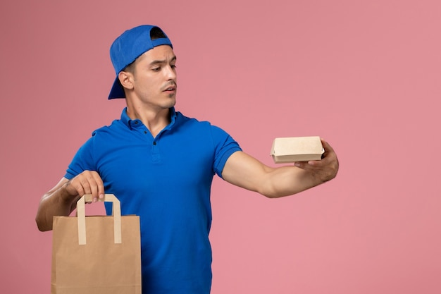 Front view young male courier in blue uniform and cape with delivery packages on his hands on the pink wall