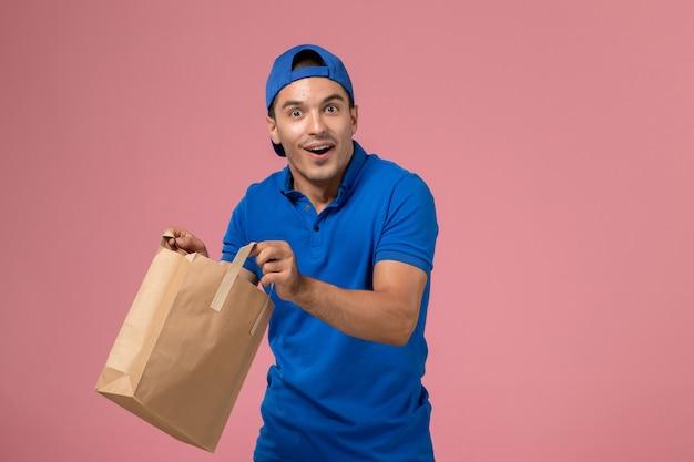 Corriere maschio giovane vista frontale in uniforme blu e mantello con pacco di carta di consegna sulle mani sulla parete rosa