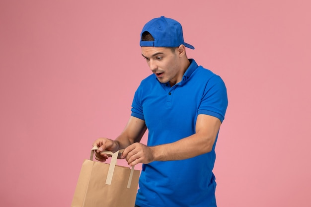 Front view young male courier in blue uniform and cape with delivery paper package on his hands on the pink wall
