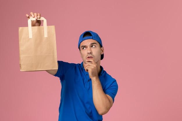 Corriere maschio giovane vista frontale in uniforme blu e mantello con pacco di carta di consegna sulle sue mani pensando sulla parete rosa