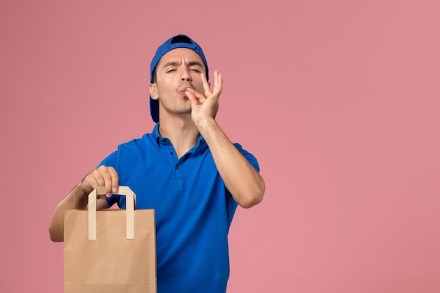 Front view young male courier in blue uniform and cape with paper delivery package on his hands on pink wall