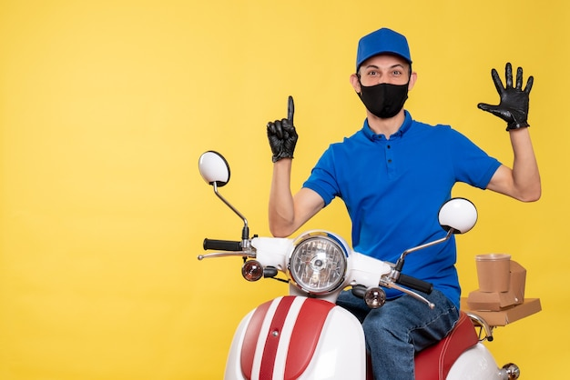 Front view young male courier in blue uniform and mask on the yellow background