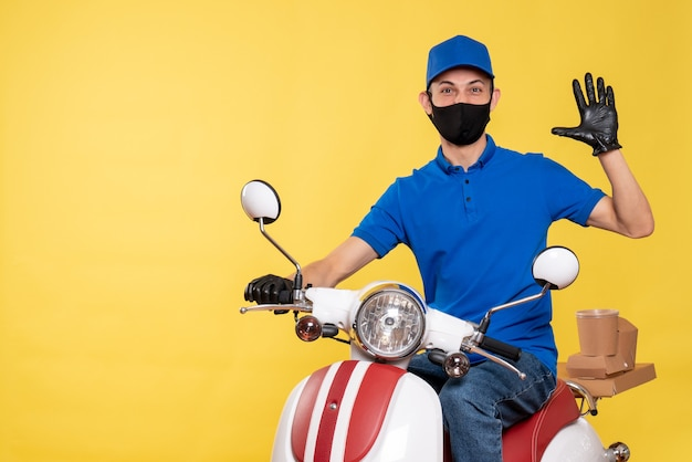 Front view young male courier in blue uniform and mask on yellow background