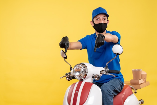 Front view young male courier in blue uniform on yellow background bike covid- pandemic service virus work delivery job