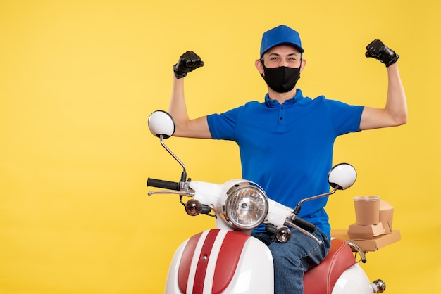 Front view young male courier in blue uniform on yellow background covid- job pandemic delivery service bike work