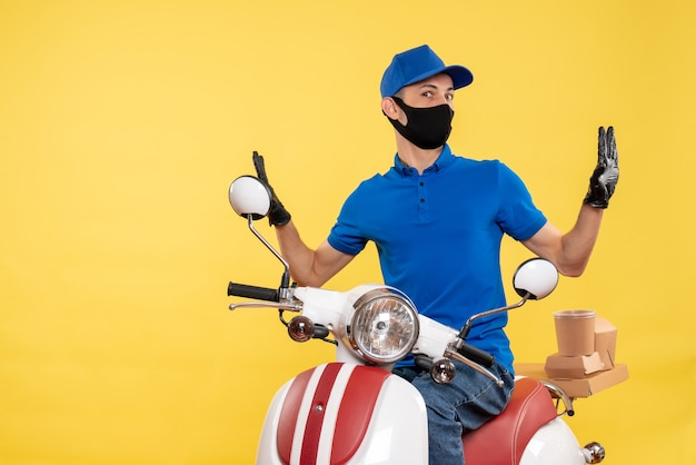 Front view young male courier in blue uniform on the yellow background covid- job pandemic delivery service virus bike work