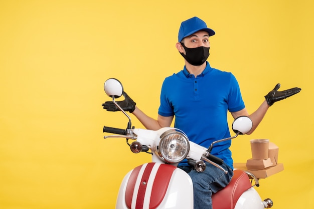 Front view young male courier in blue uniform on yellow background covid- job pandemic delivery service virus work