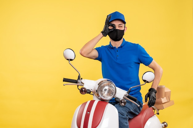 Front view young male courier in blue uniform on yellow background covid- job pandemic delivery virus bike work