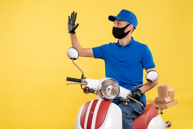 Front view young male courier in blue uniform on yellow background covid- job pandemic service virus bike work