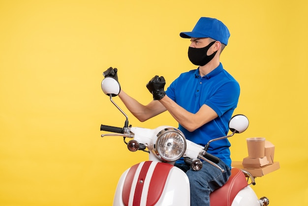 Front view young male courier in blue uniform on the yellow background covid- pandemic delivery service job virus bike work