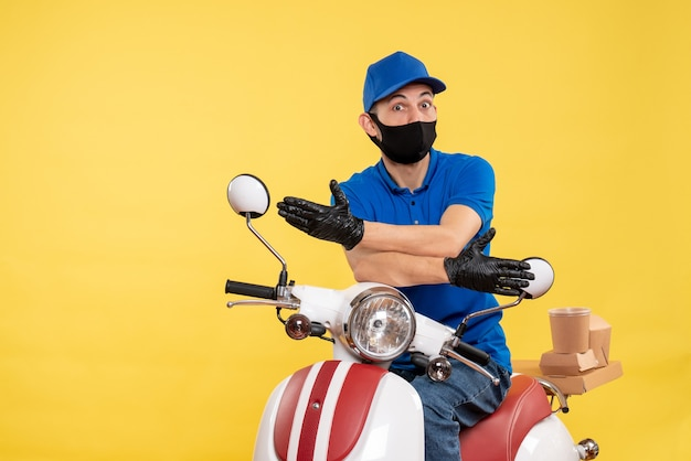 Front view young male courier in blue uniform on yellow background covid- pandemic delivery service job virus bike work