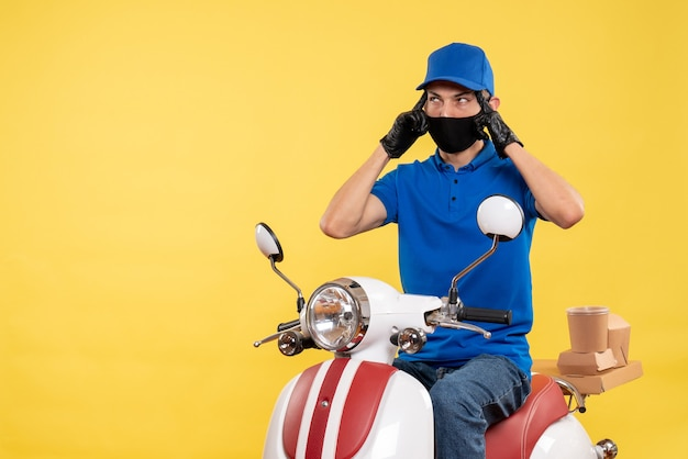 Front view young male courier in blue uniform on yellow background covid- pandemic job virus bike work delivery