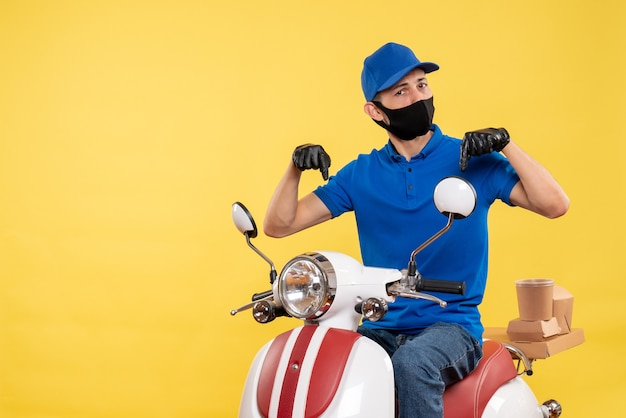 Front view young male courier in blue uniform on yellow background covid- pandemic service job bike work delivery