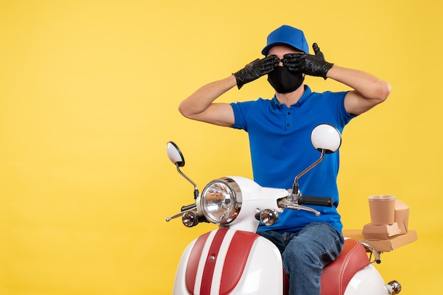 Front view young male courier in blue uniform on yellow background covid- pandemic service job virus bike delivery