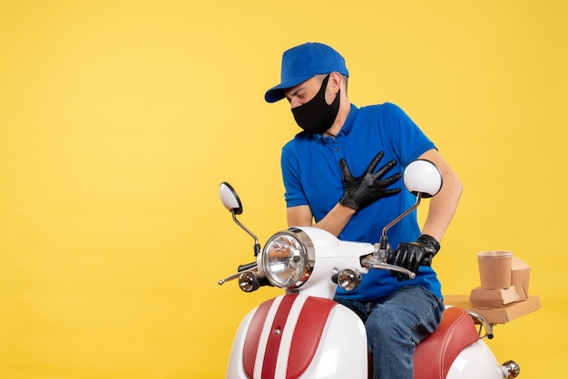 Front view young male courier in blue uniform on yellow background covid- pandemic service job virus bike work delivery pain