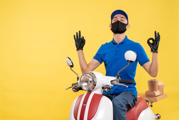 Front view young male courier in blue uniform on a yellow background covid- pandemic service job virus bike work delivery