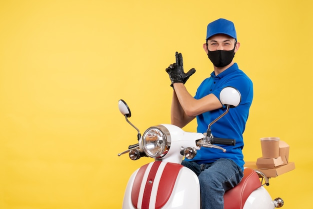 Front view young male courier in blue uniform on the yellow background covid- pandemic service job virus bike work delivery