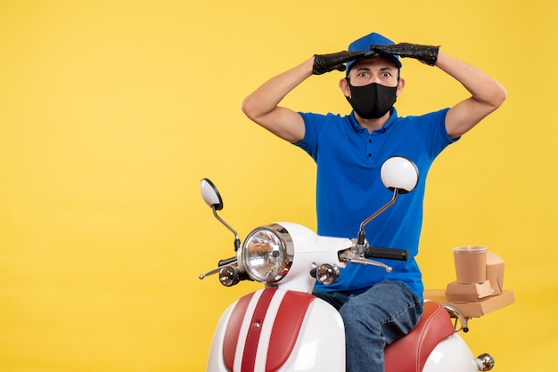 Front view young male courier in blue uniform on yellow background covid- pandemic service job virus bike work delivery