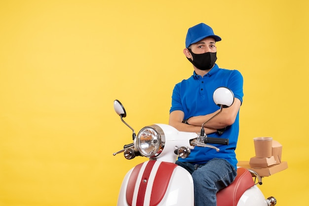 Front view young male courier in blue uniform on yellow background covid- pandemic service job virus work delivery