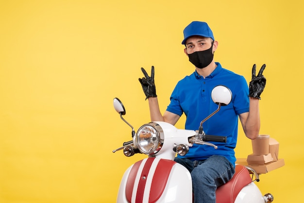 Front view young male courier in blue uniform on yellow background covid- pandemic service virus bike work delivery