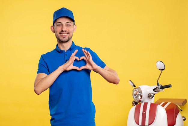 Front view young male courier in blue uniform on yellow background job service uniform bike work delivery worker color